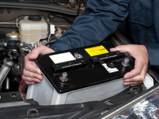 mobile mechanic installing new battery into car