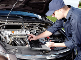 mobile mechanic using his laptop computer to diagnose a cars engine