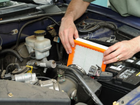 mobile mechanic installing a new air filter in a car during a routine maintenance check
