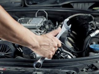 mobile mechanic holding a wrench as he works on the engine of a car
